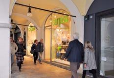 Les gens marchant devant des fenêtres de boutique et faisant des emplettes dans le portique central du XVIème siècle Photos libres de droits