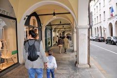 Les gens marchant devant des fenêtres de boutique et faisant des emplettes dans le portique central du XVIème siècle Photos stock
