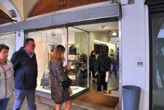 Les gens marchant devant des fenêtres de boutique et faisant des emplettes dans le portique central du XVIème siècle Images stock