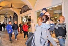 Les gens marchant devant des fenêtres de boutique et faisant des emplettes dans le portique central du XVIème siècle Photo stock
