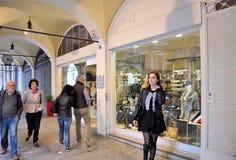 Les gens marchant devant des fenêtres de boutique et faisant des emplettes dans le portique central du XVIème siècle Photographie stock