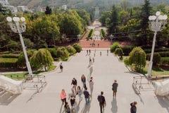 Les gens marchant en parc public vert avec la haute allée d'arbres au jour ensoleillé Photographie stock libre de droits