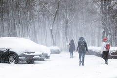 Les gens marchant par la rue de ville couverte de neige pendant les chutes de neige lourdes Tempête de neige dans la ville à l'hi images stock