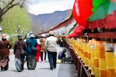 Les gens marchant près de la prière d'or battent du tambour de la rangée dans la rue de Lhasa, Thibet Image libre de droits