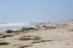 Les gens marchant sur la plage dans la distance Photo stock
