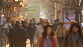 Les gens marchant sur le coucher du soleil d'or de fond dans la ville Vidéo Defocused banque de vidéos
