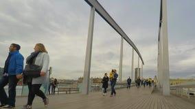 Les gens marchant sur le pilier dans le port banque de vidéos