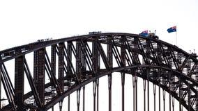 Les gens marchant sur Sydney Harbour Bridge avec onduler les drapeaux australiens photographie stock libre de droits