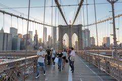Les gens marchent à travers le pont de Brooklyn au coucher du soleil à New York Photos libres de droits