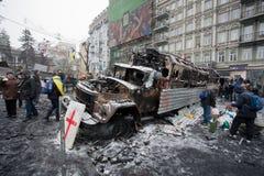 Les gens marchent autour des barricades avec les voitures militaires de burn-out sur la rue de neige pendant la protestation anti- Photo libre de droits
