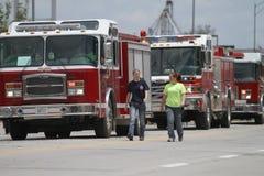 Les gens marchent avec des camions de pompiers dans un défilé en petite ville Amérique Photos libres de droits