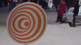 Les gens marchent derrière la roue hypnotique de rotation orange sur la neige à la rue d'hiver banque de vidéos