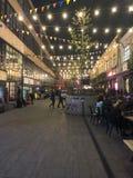 Les gens marchent le long de la rue piétonnière moderne de nuit avec les drapeaux et les ampoules, boutiques avec des cafés la Gé images stock