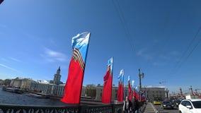 Les gens marchent le long du pont de palais, décoré des drapeaux de fête sur Victory Day banque de vidéos