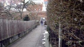 Les gens marchent sur le chemin de ville le jour nuageux d'automne Art Les gens marchent le long du chemin entre la barrière et l banque de vidéos