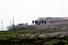 Les gens marchent sur le pilier de la Hollande de fourgon de Hoek image libre de droits