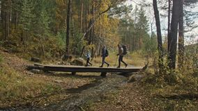 Les gens marchent sur un pont en bois au-dessus de la rivière voyages de famille Environnement de personnes par des montagnes, ri banque de vidéos