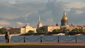 Les gens marchent sur un remblai sur l'Amirauté et le fond de pont de palais Photos stock