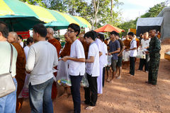Les gens mettent la nourriture offrant à l'aumône de moine bouddhiste la cuvette qui est photographie stock libre de droits