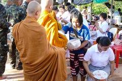 Les gens mettent la nourriture offrant à l'aumône de moine bouddhiste la cuvette qui est photographie stock