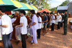Les gens mettent la nourriture offrant à l'aumône de moine bouddhiste la cuvette qui est photo libre de droits