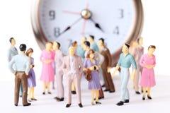 Les gens miniatures de jouet restent l'horloge d'alarme proche Images stock
