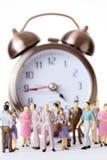 Les gens miniatures de jouet restent l'horloge d'alarme proche Photos libres de droits