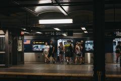 Les gens montant dans le train à la 14ème station de métro de rue à New York, Etats-Unis photo stock