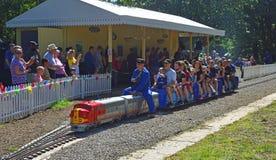 Les gens montant le train au chemin de fer miniature dans le St Neots de parc de côté de rivière Photo libre de droits