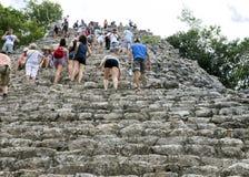 Les gens montant un bas que la pyramide de Nohoch Mul dans le Coba ruine Images libres de droits