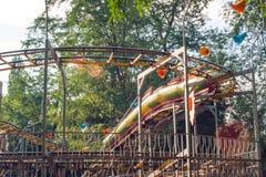 Les gens montent sur des montagnes russes en parc d'attractions image libre de droits
