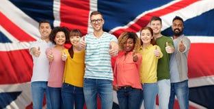 Les gens montrant des pouces au-dessus de drapeau anglais Photos libres de droits