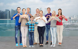 Les gens montrant la main de coeur signent plus de le bord de l'eau de ville Images stock