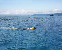 Les gens naviguant au schnorchel en mer bleue ouverte Photos stock