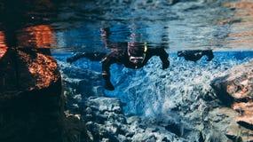 Les gens naviguant au schnorchel et plongeant dans l'eau glaciaire clair comme de l'eau de roche bleue en parc national Islande d photographie stock libre de droits