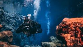 Les gens naviguant au schnorchel et plongeant dans l'eau glaciaire clair comme de l'eau de roche bleue en parc national Islande d image stock