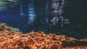 Les gens naviguant au schnorchel et plongeant dans l'eau glaciaire clair comme de l'eau de roche bleue en parc national Islande d images stock