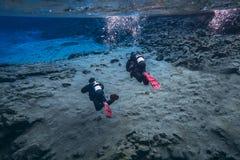 Les gens naviguant au schnorchel et plongeant dans l'eau glaciaire clair comme de l'eau de roche bleue en parc national Islande d photo stock