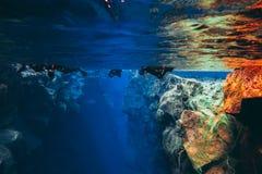 Les gens naviguant au schnorchel et plongeant dans l'eau glaciaire clair comme de l'eau de roche bleue en parc national Islande d photos libres de droits