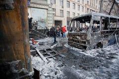 Les gens nettoient la rue d'hiver avec les autobus couverts de glace brûlés dans les combats avec des pelotons de police pendant l Photo libre de droits