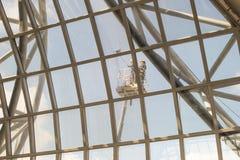 Les gens nettoyant en dehors de des fenêtres d'aéroport Image stock