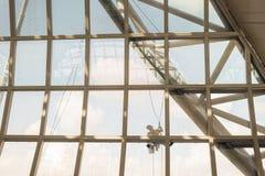 Les gens nettoyant en dehors de des fenêtres d'aéroport Photographie stock libre de droits