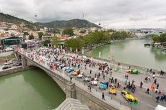 Les gens observant l'exposition extérieure de rétros voitures sur le vieux pont par la rivière Kura photo stock