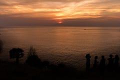 Les gens observant le coucher du soleil Photos libres de droits