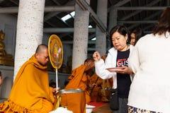 Les gens offrent le riz sur la cuvette d'aumône de moine bouddhiste images stock