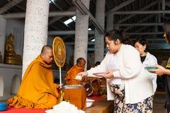Les gens offrent le riz sur la cuvette d'aumône de moine bouddhiste photographie stock libre de droits