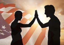 Les gens ombragent la haute fiving contre le drapeau américain photos libres de droits