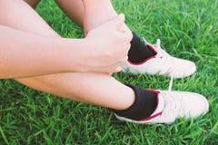 Les gens ont étreint ses genoux sur le vert d'herbe photographie stock libre de droits