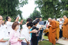 Les gens ont mis des offres de nourriture dans l'aumône de moine bouddhiste roulent pour faire photographie stock