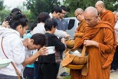 Les gens ont mis des offres de nourriture dans l'aumône de moine bouddhiste roulent pour faire photo libre de droits
